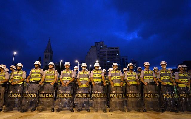 Cảnh sát đứng bảo vệ khi người biểu tình diễu hành phản đối World Cup 2014 và yêu cầu dịch vụ công cộng tốt hơn ở Sao Paulo, Brazil.
