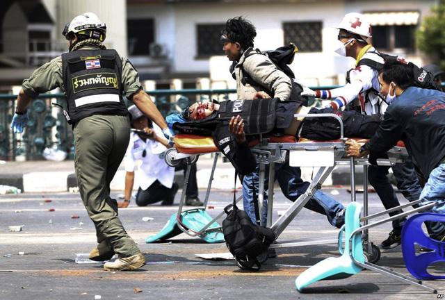Nhân viên cứu hộ đưa một cảnh sát bị thương sau một vụ nổ trong cuộc đụng độ với người biểu tình chống chính phủ ở Bangkok, Thái Lan.