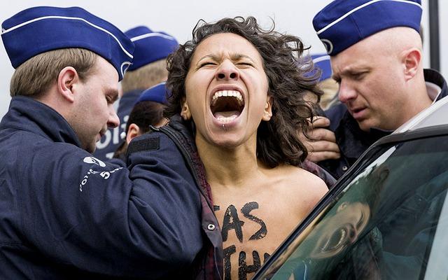 Cảnh sát bắt giữ một người biểu tình chống Nga thuộc nhóm Femen bên ngoài cuộc họp khẩn cấp của các Ngoại trưởng Liên minh châu Âu ở Brussels, Bỉ.