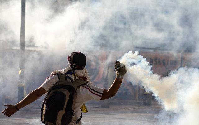 Một người biểu tình ném lựu đạn hơi cay vào cảnh sát ở Altamira, phía đông Caracas, Venezuela.
