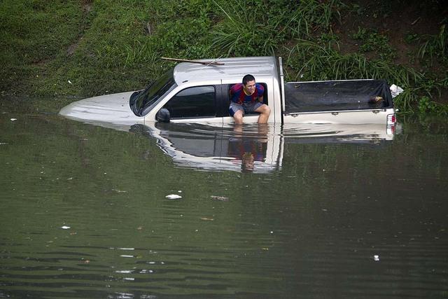 Một người đàn ông chờ giúp đỡ khi chiếc ô tô bán tải bị ngập trong nước ở Cali, Colombia.