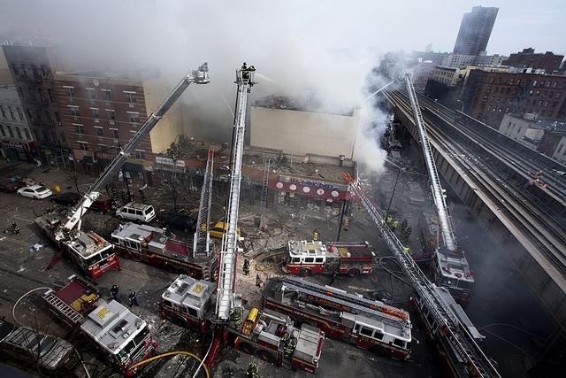 Lính cứu hỏa chiến đấu với hỏa hoạn sau khi một tòa nhà bị sập ở New York, Mỹ.