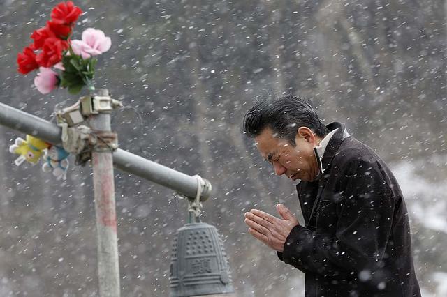 Một người đàn ông cầu nguyện trước lối vào trường Tiểu học Okawa, ngôi trường mất 74 trong tổng số 108 học sinh trong thảm họa động đất và sóng thần ở Nhật Bản vào năm 2011.