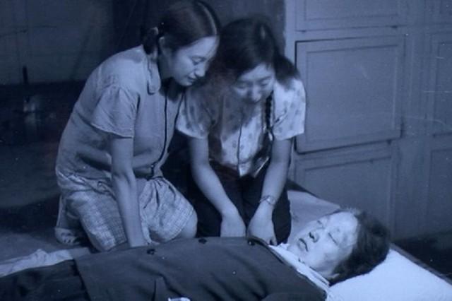Các con cô giáo Biện Trọng Vân khóc trước thi thể mẹ sau khi bà bị các Hồng vệ binh đánh chết