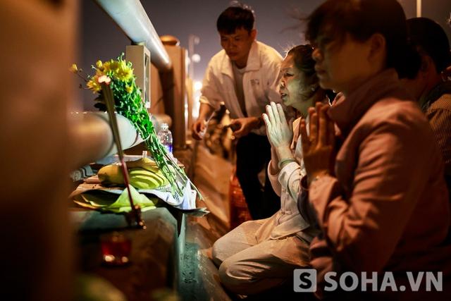 Các thành viên trong gia đình làm lễ tại cầu Thanh Trì vào tối 13/4.