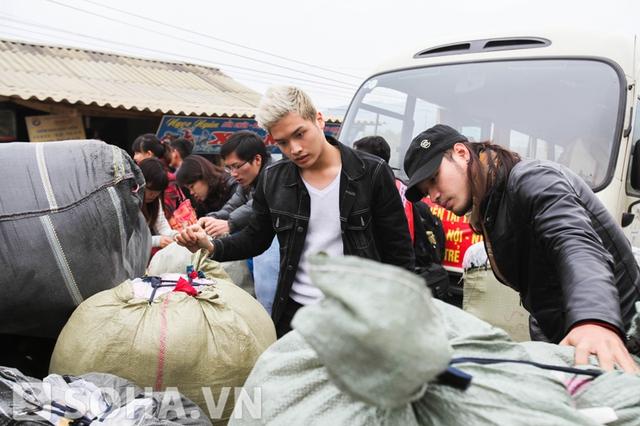 Hai chàng trai trẻ cùng các thành viên của đoàn từ thiện phân loại quà để gửi đến các em nhỏ.