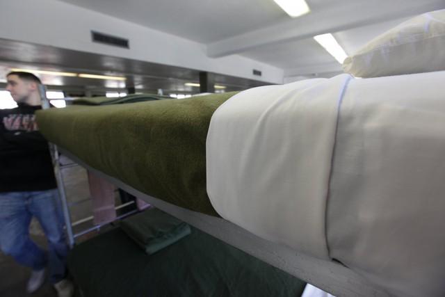 Khăn trải giường và chăn được gấp nếp theo đúng quy định.