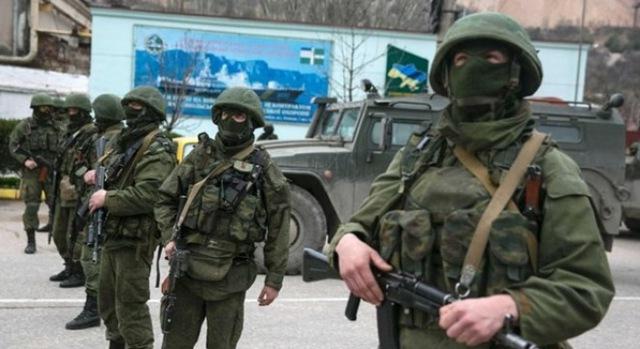 Các binh sĩ đứng cạnh một xe thiết giáp của Nga bên ngoài một chốt kiểm soát biên giới Ukraine tại thành phố Balaclava, Crimea. (Ảnh: Reuters)