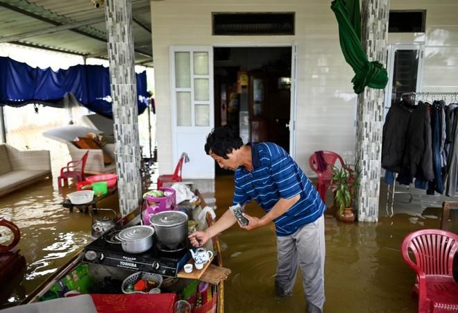 24h qua ảnh: Người đàn ông pha trà trong ngôi nhà ngập lụt ở Việt Nam - Ảnh 2.