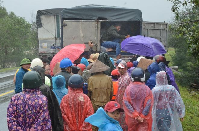 Người dân dầm mưa bên quốc lộ xin cứu trợ, giúp qua cơn đói ở Quảng Bình - Ảnh 2.