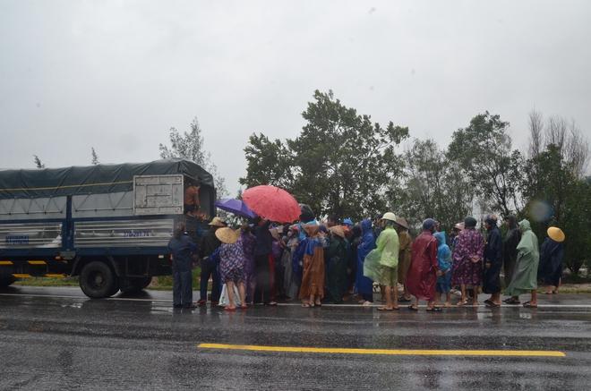 Người dân dầm mưa bên quốc lộ xin cứu trợ, giúp qua cơn đói ở Quảng Bình - Ảnh 1.