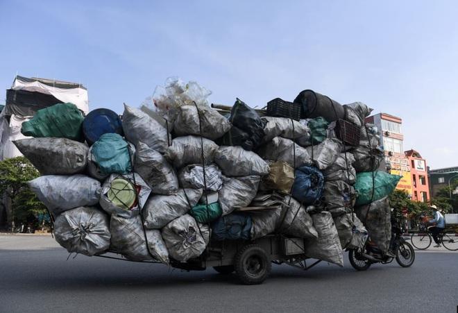 24h qua ảnh: Xe máy kéo xe bò chở rác tái chế trên đường phố ở Hà Nội - Ảnh 2.