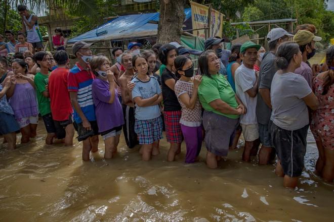 24h qua ảnh: Dân Philippines xếp hàng nhận cứu trợ trong nước lũ - Ảnh 5.