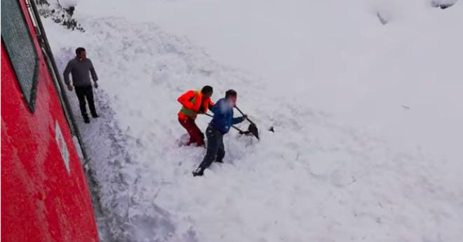 Đoàn tàu rú còi inh ỏi rồi dừng lại, nhân viên lao xuống hối hả cào tuyết và làm nên điều diệu kỳ - Ảnh 2.