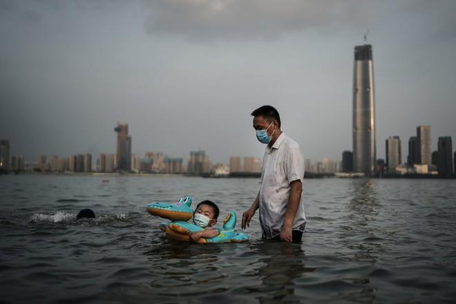 24h qua ảnh: Cậu bé đeo khẩu trang bơi trong công viên ngập lụt do nước sông dâng cao ở TQ - Ảnh 2.