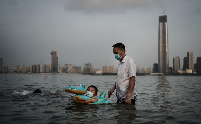24h qua ảnh: Cậu bé đeo khẩu trang bơi trong công viên ngập lụt do nước sông dâng cao ở TQ