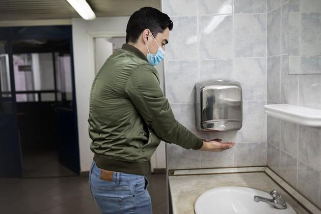 Làm khô tay bằng giấy hay máy sấy ít lây truyền mầm bệnh hơn: Câu trả lời sẽ gây ngỡ ngàng - Ảnh 1.