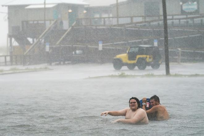 Bão Sally đổ bộ vào Mỹ: Bãi đỗ xe thành bể bơi khổng lồ, người dân bơi lội dưới mưa lớn - Ảnh 3.