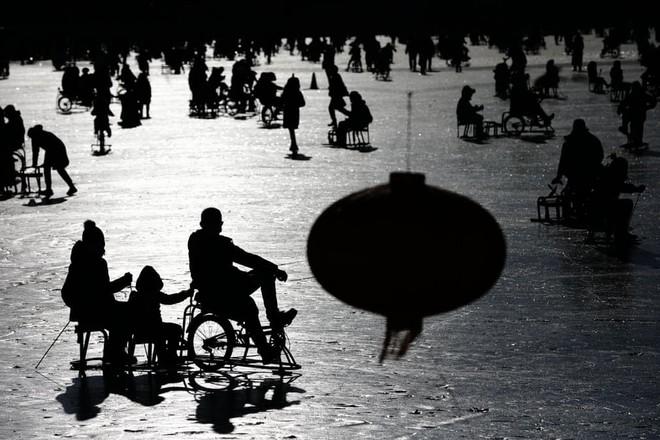 24h qua ảnh: Người bán hoa giả đạp xe trên cầu Long Biên - Ảnh 7.