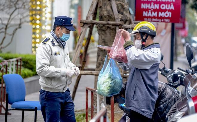 Ảnh: Người dân tiếp tế lương thực cho toà chung cư có người mắc COVID-19 ở Times City, Hà Nội