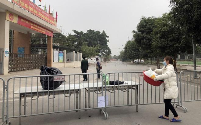 Hàng rào an ninh được bố trí xung quanh Trường tiểu học Xuân Phương, dân quân hỗ trợ chuyển đồ đạc vào trong
