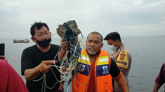 Những hình ảnh đầu tiên về các mảnh vỡ được cho là của máy bay Indonesia vừa gặp nạn - Ảnh 6.