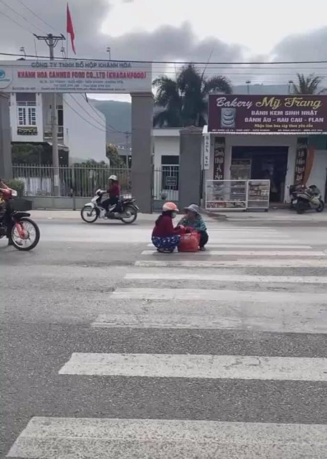 Mặc kệ xe cộ qua lại, 2 người phụ nữ ngồi xổm giữa đường buôn chuyện với nhau - Ảnh 2.