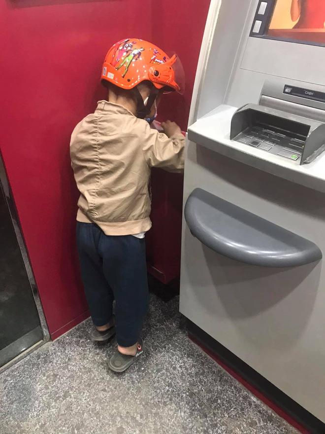 Cậu bé nhặt hóa đơn rút tiền rồi cho vào thùng rác.