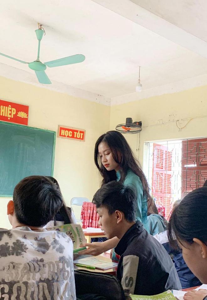 Cô giáo diện chiếc áo dài màu xanh, tóc xoăn xõa xuống và đang cúi đầu chăm chú kiểm tra vở của học sinh.