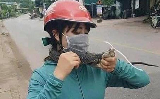 Đang đi vợ bỗng nhảy xuống xe, tay không bắt con rắn dài cả mét khiến chồng kinh hãi