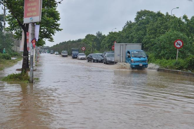 [Ảnh] Đường gom Đại lộ Thăng Long ở Hà Nội chìm trong biển nước sau trận mưa lớn đầu mùa - Ảnh 7.
