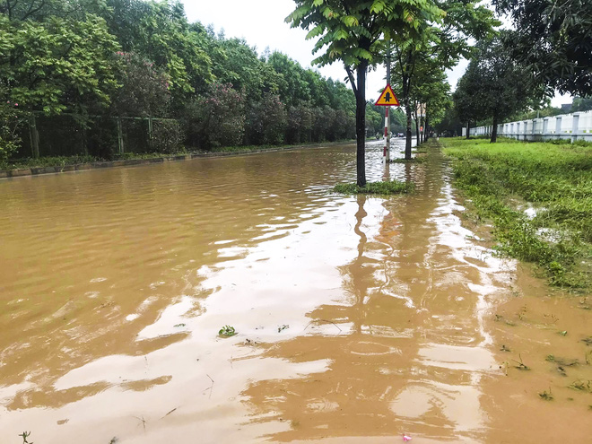 [Ảnh] Đường gom Đại lộ Thăng Long ở Hà Nội chìm trong biển nước sau trận mưa lớn đầu mùa - Ảnh 9.