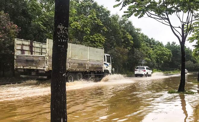 [Ảnh] Đường gom Đại lộ Thăng Long ở Hà Nội chìm trong biển nước sau trận mưa lớn đầu mùa - Ảnh 10.