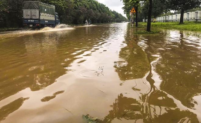 [Ảnh] Đường gom Đại lộ Thăng Long ở Hà Nội chìm trong biển nước sau trận mưa lớn đầu mùa - Ảnh 11.