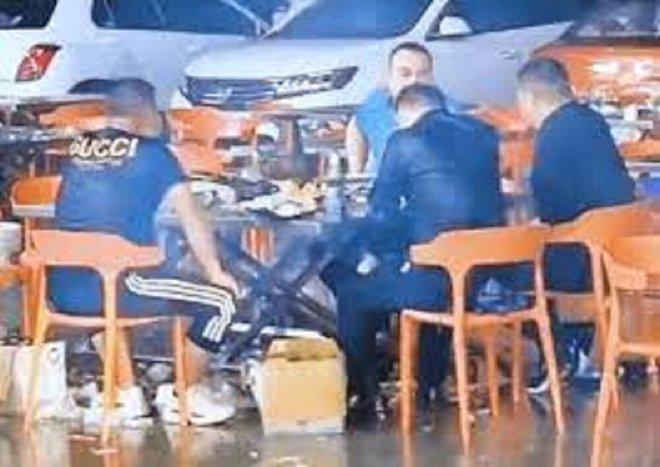Lạ đời 4 người đàn ông ngồi ăn lẩu dưới trời mưa như trút nước - Ảnh 1.