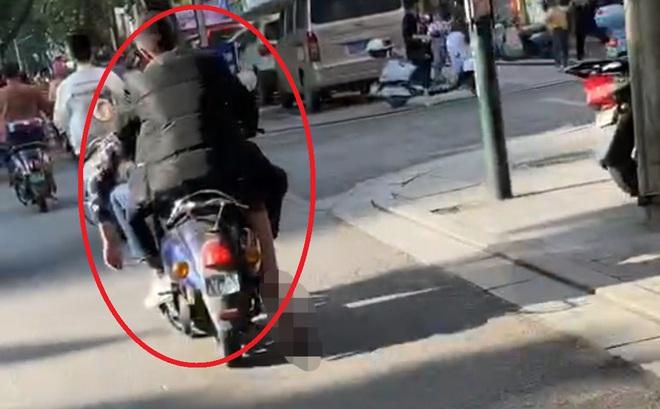 Người đàn ông điều khiển xe máy chở thi thể ngay trên đường phố, chân người chết bị kéo lê suốt dọc đường