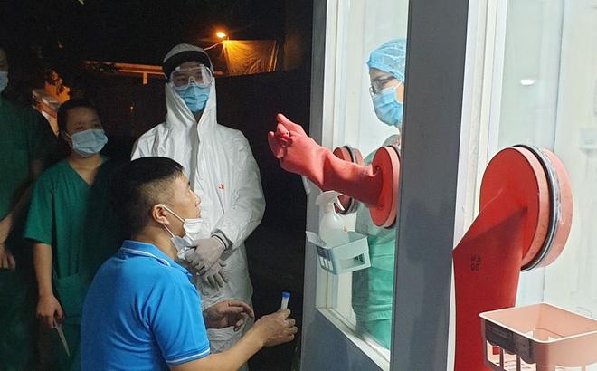 Nhân viên y tế huyện Tân Yên thử nghiệm quy trình tại buồng lấy mẫu xét nghiệm chống nóng. Ảnh: Thu Quỳnh.