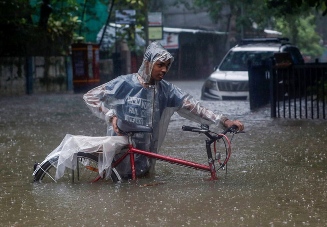 7 ngày qua ảnh: Người đàn ông dắt xe đạp trên đường phố ngập lụt - Ảnh 2.