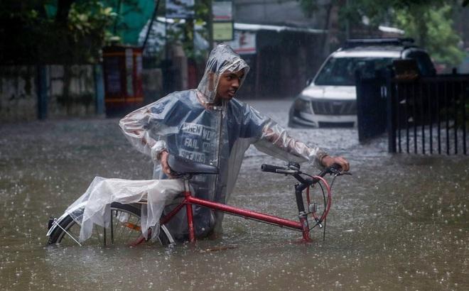 7 ngày qua ảnh: Người đàn ông dắt xe đạp trên đường phố ngập lụt