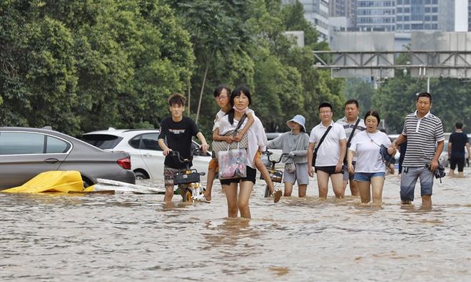 NÓNG: Hàng loạt địa phương ở Hà Nam, Trung Quốc báo động đỏ - Ô tô chồng chất trên đường ở Trịnh Châu sau lũ - Ảnh 1.