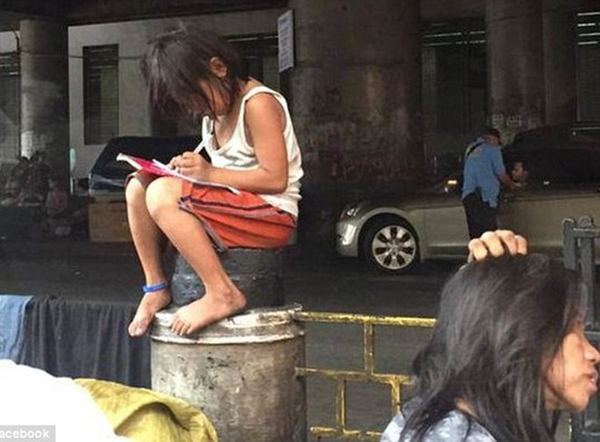 Bé gái mải mê làm bài tập trên đường phố gây sốt trên mạng xã hội