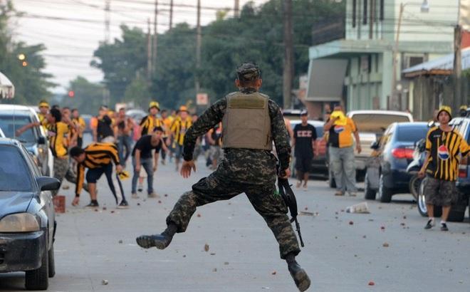 """24h qua ảnh: Lính chống bạo động hứng cơn mưa """"củ đậu bay"""" từ cổ động viên bóng đá"""