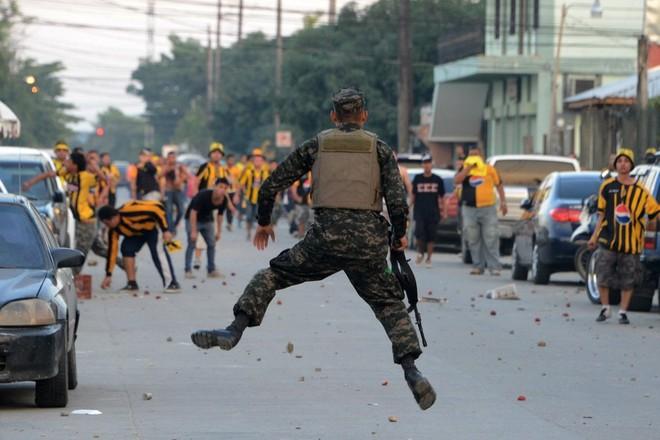 24h qua ảnh: Lính chống bạo động hứng cơn mưa củ đậu bay từ cổ động viên bóng đá - Ảnh 3.