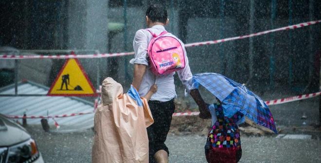 Giữa cơn mưa lớn, hình ảnh 3 cha con khiến người ta xúc động