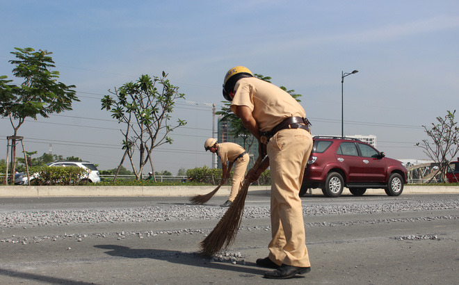 Cảnh sát giao thông đội nắng quét đá rơi vãi trên đường ở Sài Gòn