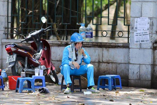 Người Hà Nội mặc bìa carton, hai tay hai ô giữa ngày nắng nóng lịch sử - Ảnh 6.