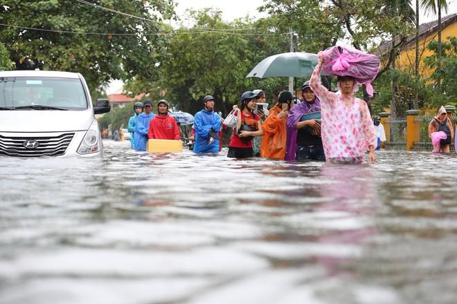 Du khách nước ngoài thích thú lội nước, chụp hình trong lũ ở Hội An - Ảnh 2.