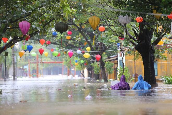 Du khách nước ngoài thích thú lội nước, chụp hình trong lũ ở Hội An - Ảnh 1.