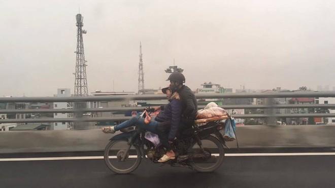 Tranh cãi về hình ảnh anh chồng ôm chặt cô vợ đang ngã lưng ngủ trước đầu xe máy - Ảnh 1.