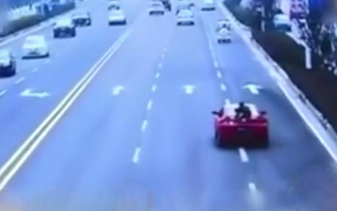 Cô gái trẻ bám chặt đuôi xe ô tô kêu cứu trên cao tốc khiến người đi đường thất kinh - Ảnh 1.